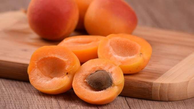 Abricots entiers et coupés en deux sur une planche de bois en gros plan