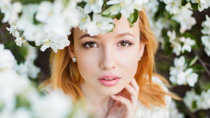 Jeune femme très jolie suite à des injections d'acide hyaluronique. Elle a les cheveux roux et regarde à travers les branchages d'un arbre en fleur.