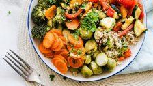 Alimentation alcaline : un plat est posé sur une table en bois à côté d'une fourchette. Il est rempli de légumes, de quinoa et d'herbes fraîches.
