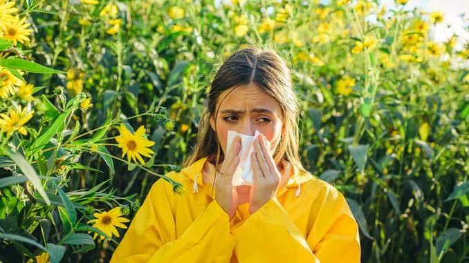 Une jeune femme souffle sur une fleur de pissenlit, le pollen vole tout autour d'elle.