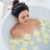 Une femme brune prend un bain contre l'eczéma. L'eau est trouble et à la surface flotte des fleurs jaunes.