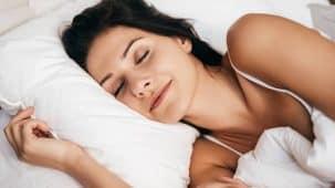 Femme en train de dormir paisiblement, le sourire aux lèvres, sur un lit, oreiller, couette blancs. La luminosité de l'image fait penser au bien-être.