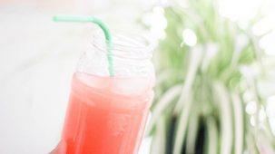 Boisson rose dans un bocal en verre avec une paille en gros plan. Plante verte en arrière plan flou