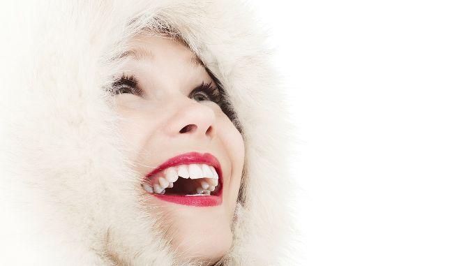 Femme en capuche qui sourit en regardant vers le ciel, heureuse