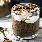 Une verrine remplie de pudding de chia au chocolat, avec une couche de fromage blanc saupoudrée de céréales croustillantes. La verrine est posée sur une table en bois, il y a une cuillère en métal à côté de la verrine.