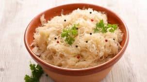 Chou fermenté de la choucroute dans un bol et chou entier en arrière plan sur une planche en bois