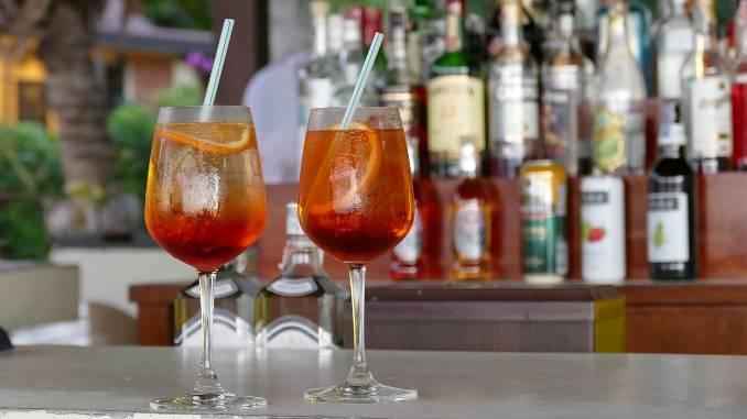 2 cocktails sur un bar avec des bouteilles d'alcool en fond