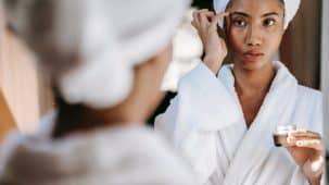 Une femme s'applique du collagène sur le visage. Elle est en peignoir et se regarde dans un miroir.