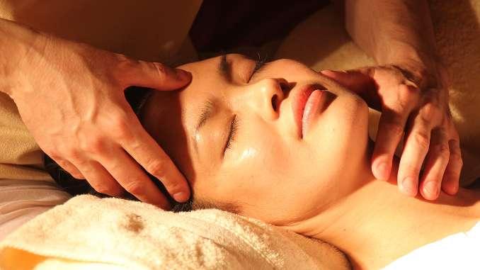 Femme détendue pour une séance de rélexologie faciale (dien chan). Les mains du reflexologue sont sur son visage pour favoriser le bien-être.