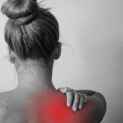 Femme de dos qui se tient l'épaule avec la main. La zone est en rouge pour indiquer une douleur, une inflammation de l'articulation.