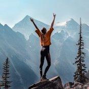 Femme heureuse debout sur un rocher, les bras levés face à la nature montagneuse et au ciel dégagé.