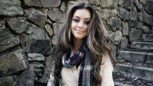 Jeune femme jolie : pose naturelle avec une écharpe. Jolie cadre avec mur et escalier en pierre à l'extérieur.