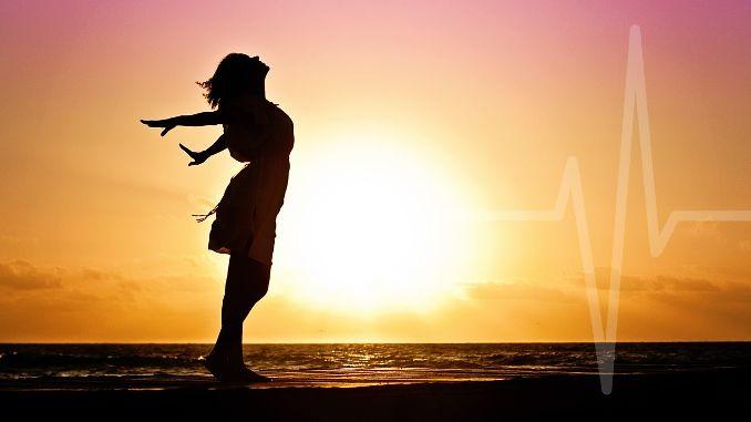 Femme qui inspire profondément les bras grand ouverts sur la plage avec le soleil et la mer en arrière plan. Rythme cardiaque discret qui se fond avec le décor.