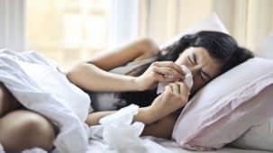 Femme brune qui se mouche avec un mouchoir. Elle est malade, un plaid sur les épaules, dans une pièce avec du bois aux murs.