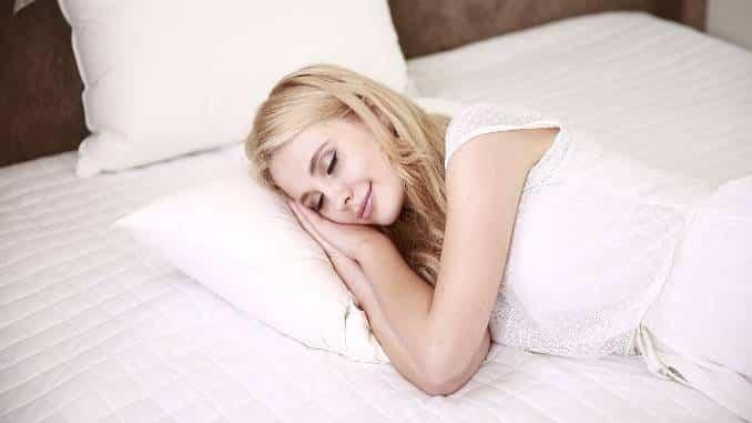 Femme blonde qui dort dans un lit blanc. Petite sourire aux lèvres.