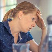 Femme stressée et anxieuse. Elle se tient le front, assise devant son travail à accomplir.