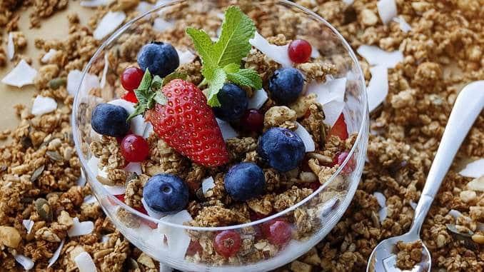 Aliments riches en fibres : il y a un bol en verre rempli de muesli sur une table recouverte de céréales. Le bol de muesli contient également des myrtilles, des fraises ainsi que des copeaux de noix de coco et une feuille de menthe fraîche.