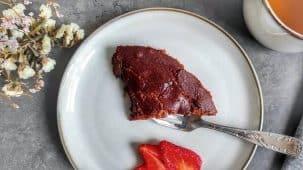 Une part de fondant au chocolat sur une assiette fleurie, avec des plantes en arrière plan et des amandes sur le côté.