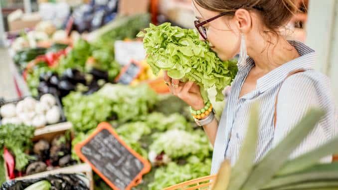 Fruits et légumes stand marché avec personne qui fait ses achats