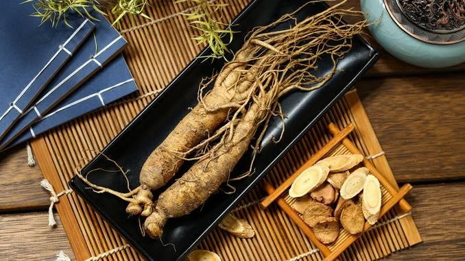 Racines de ginseng dans un récipient noir, présentés sur une table en bois. Des tranches de ginseng sont posées à côté.