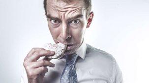 Homme qui grignote un biscuit avec honte. Tâche de sauce rouge sur sa cravate