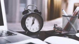 Réveil noir, type horloge, posé sur un bureau noir. Ordinateur portable, livre ouvert, stylos, lunettes, portefeuille.