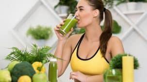 Gros plan sur un jus vert dans un verre. Tout autour, il y a des fruits et légumes : pommes vertes et rouges, salade, brocolis.