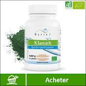 Klamath bio : boite de compléments alimentaires (gélules) de la marque française Dynveo. Fond blanc avec la poudre de klamath en arrière plan, derrière la boite. La mention acheter est sur fond vert, en bas de l'image.