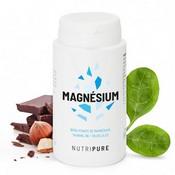 Flacon de magnésium blanc sur fond blanc, à sa droite il y a des feuilles vertes. À la gauche du produit, il y a du chocolat et des noisettes.