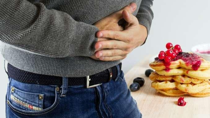 Homme qui se tient le ventre avec les deux mains sur son ventre. Plan de près, on aperçoit seulement le haut de son jean, sa ceinture et son ventre sous un pull. On imagine une douleur abdominale. Des pancakes sont présentés en arrière plan.