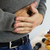 Homme qui se tient le ventre avec les deux mains sur son ventre. Plan de près.