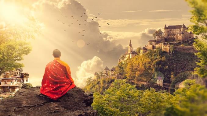 Méditation dans un cadre naturel asiatique. Un homme assis sur un rocher avec vue de haut sur des constructions en pleine nature.