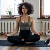 Une femme métisse fait de la méditation dans son appartement ur un tapis au sol. Elle a les jambes qui se croisent et la tête haute.
