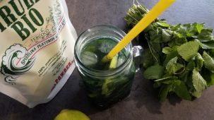 Verre de Mojito Spiruline entouré d'un sachet de spiruline, de feuilles de menthe et d'un citron.