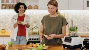 Deux jeunes femmes préparent un jus vert dans leur cuisine pour nettoyer le foie naturellement.