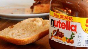 Pot de nutella posé sur une table avec une tartine de pain et une assiette en arrière plan.