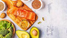 Aliments sources d'oméga-3 : il y a des graines, des oléagineux, du poisson, des pousses vertes, des oeufs et un avocat disposés sur une table.
