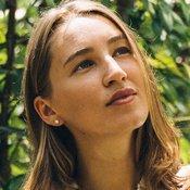 Une femme avec une très belle peau regarde vers le haut. On aperçoit des arbres derrière elle