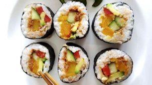 6 makis en gros plan sur fond blanc. Sushis (makis) colorés grâce aux ingrédients : algue, riz, concombre, avocat, potiron, poivron, graines de sésame et tapenade de tomates.