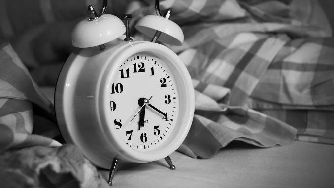 Horloge réveil posée sur un lit. Photo en noir et blanc