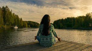 Femme assise en tailleur face à un paysage naturel (lac, forêt, coucher de soleil). Santé, bien-être et détente.