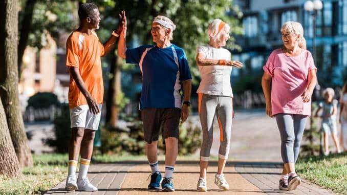 Un homme âgé porte un jogging violet et une casquette grise. Il fait de la musculation dans un parc public pour lutter contre la sarcopénie.