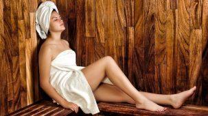 Femme en serviette blanche assise dans un sauna en bois
