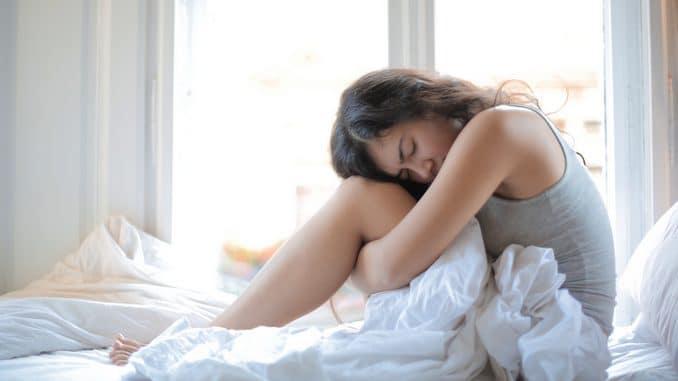 Femme blonde assise sur un canapé qui souffre de douleurs de règles, dûes au SOPK. Elle a la main sur le ventre.