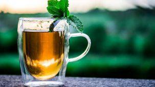 Tasse de thé avec feuilles de menthe sur le bord. Fond de verdure flou.