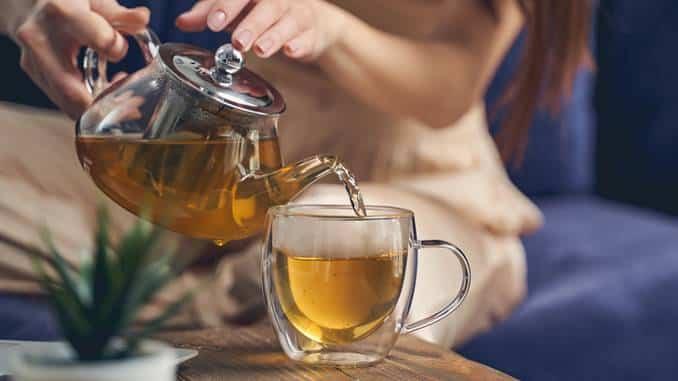 Thé dans une théière posée sur une table foncée. Une tasse de thé se situe à côté de la théière. Derrière, se trouvent des fleurs jaunes.