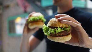 Homme tenant deux hamburgers végétariens dont un est en gros plan dans sa main