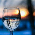 Verre d'eau en premier plan avec paysage flou derrière. Arbres, coucher de soleil et paysage bleuté.