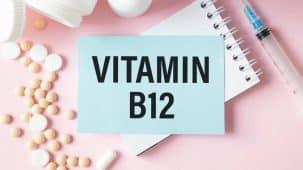 """Vitamine B12 : """"B12"""" écrit avec des comprimés posés sur un fond de bois clair. La boîte des comprimés est au dessus."""