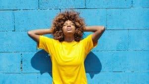 Une femme afro-américaine fait le plein de vitamine D. Elle s'expose au soleil , le dos contre un mur bleu. Elle porte un t-shirt jaune.